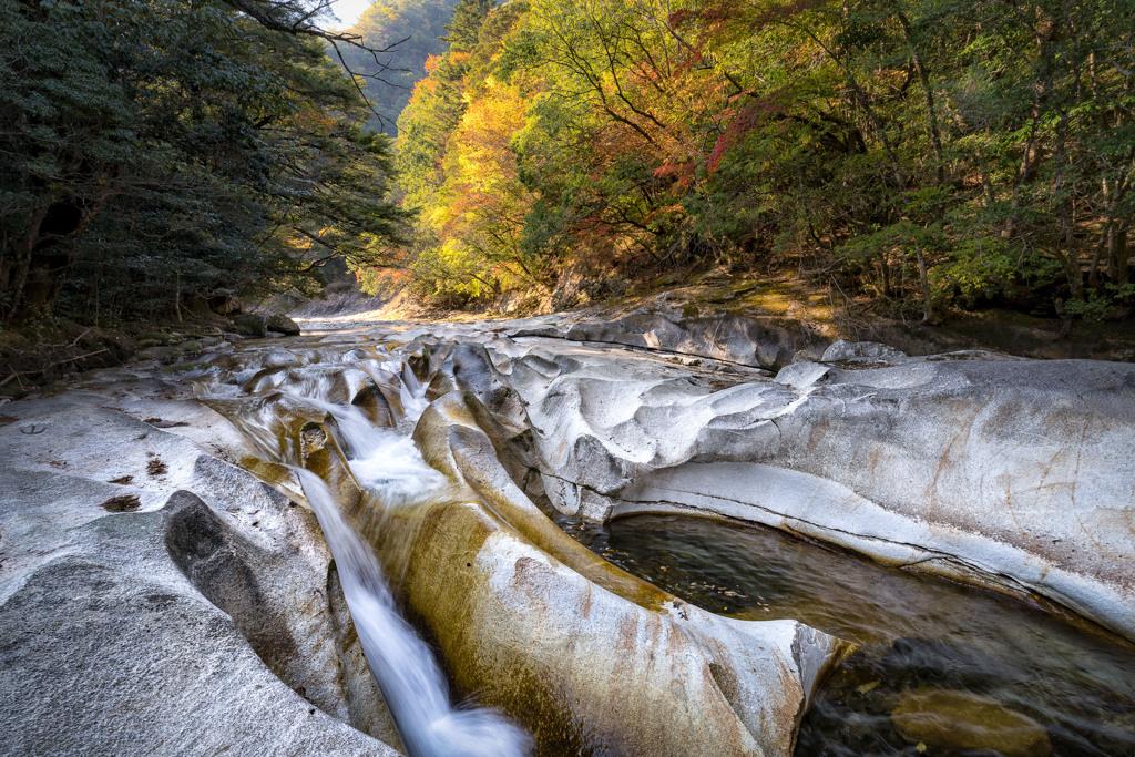 紅葉と岩間の水流れ