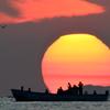 富山湾の端から登る朝日を横切る漁船に乗っている漁師さんと同じ朝日を見ている