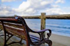 ペンキのはげたベンチと西日があたる雲と冬の海岸