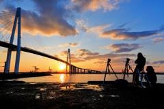 夕日と大橋と雲とカメラマン