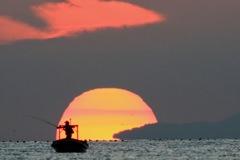 富山湾の端から登る朝日に目もくれず釣りに集中する釣り人を撮ろうと集中している時間