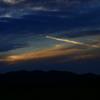 飛行機雲織り成す夕陽