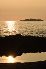 潮だまりに映る夕日と軍艦島