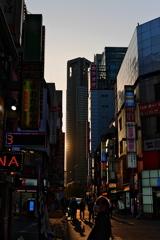ビルの隙間に差し込む新宿の夕日と男性の哀愁