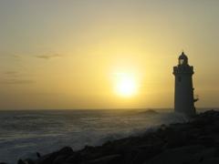夕陽と灯台と荒波